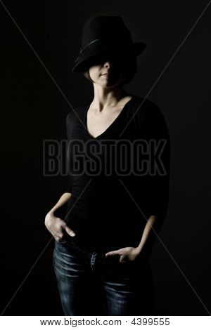 Attractive Girl On Black Hat And Jeans Against Dark Background