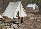 A Civil War Era Infantry Encampment with tents and fire pit. poster
