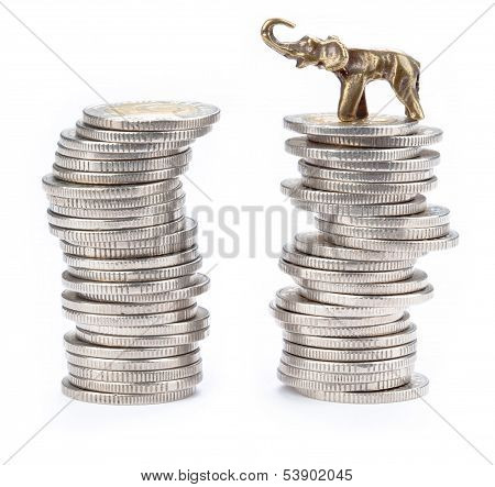 Two pyramids made with coins and lucky elephant