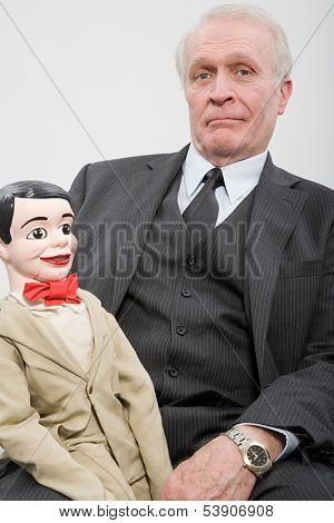 Businessman holding ventriloquists dummy