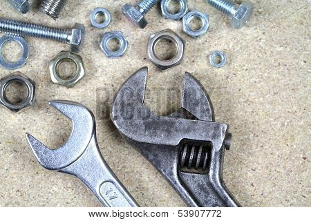 Wrench, monkey wrench and various bolts and nuts.