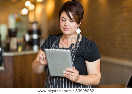 Beautiful female owner using digital tablet in cafe poster