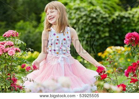 Laughing little girl dressed in suit with puffy skirt stand among rosebushes in summer park