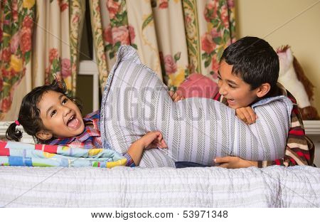 Siblings Enjoying a Pillow Fight at Home poster