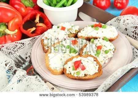Sandwiches with cottage cheese and greens on plate on wooden table close-up
