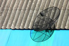 Black Satellite Dish On The Old Roof