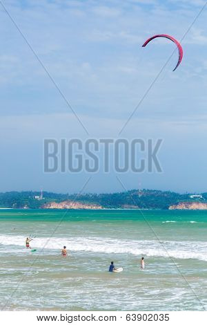 WELIGAMA, SRI LANKA - MARCH 7, 2014: Tourists swimming and kitesurfing in the sea. Tourism and fishing are two main business in this town.