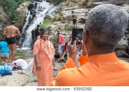 RAVANA FALLS, SRI LANKA - MARCH 2, 2014: Local tourist taking photos with mobile phone at Ravana falls, popular sightseeing attraction and one of the widest falls in the country.