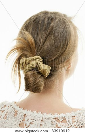 Studio shot of young woman with casual messy chignon hairstyle