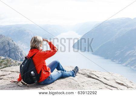 Woman sitting on Pulpit Rock / Preikestolen, Norway