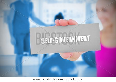 Fit blonde holding card saying self govenment against trainer and client in fitness studio