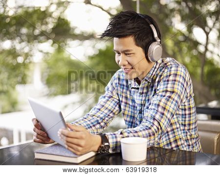Young Man Using Tablet In Coffee Shop
