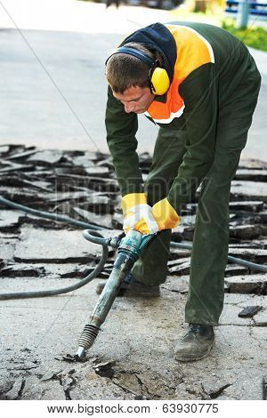 Builder worker with pneumatic jack hammer drill equipment breaking asphalt at construction road works