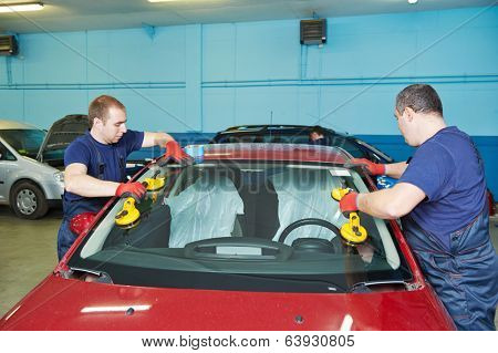 Automobile glaziers workers replacing windscreen or windshield of a car in auto service station garage poster