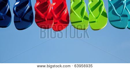 Blue, red, green and turquoise flipflops hanging with a sky background