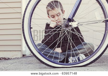 Sad boy looking at his flat bike tire
