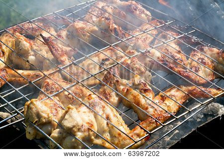 Grilling chicken on a barbecue in smoke