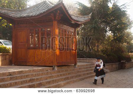 Traditional Chinese Naxi Dressed Woman Walking Through Lijiang Dayan Old Town.