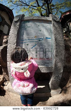Young Girl Looking Stone Map In Lijiang Dayan Old Town..