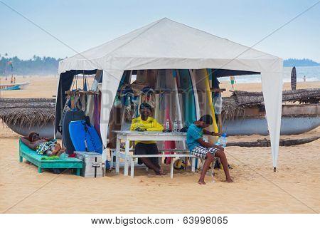 HIKKADUWA, SRI LANKA - FEBRUARY 20, 2014: Local men renting surf boards at Weligama beach, a well-known international destination for board-surfing.
