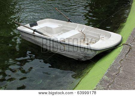 Small Boat Next to a Concrete Pier