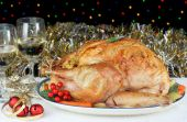 One whole roasted and stuffed turkey in a Christmas evening setting with bokeh lights in the background. poster