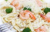 Shrimp and fettuccine alfredo with broccoli in a macro image. poster