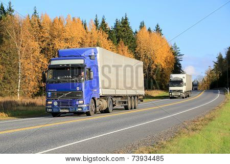 Three Trucks Platooning On A Highway In Autumn