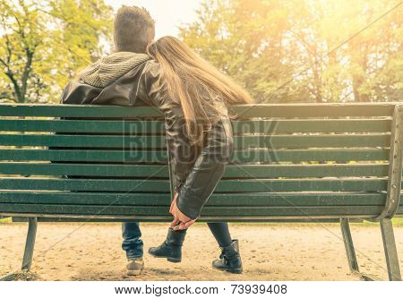 Couple on a bench - Two lovers sitting on a bench in a park and holding themselves by hands - Concepts of autumnlovetogethernessrelationship poster