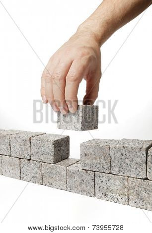 Man building a wall made of small blocks of granite rock.
