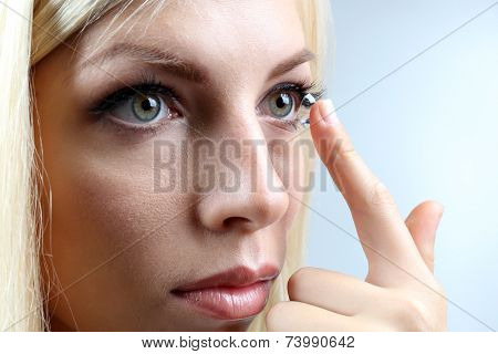 Medicine and vision concept - young woman with contact lens, close up