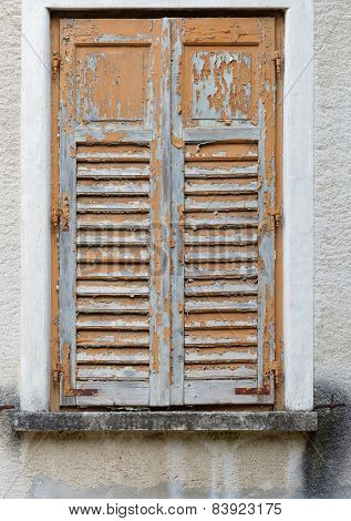Closed old window covered by wooden blinds with peeling paint