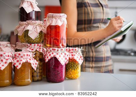Closeup On Jars With Homemade Fruits Jam And Pickled Vegetables And Housewife Writing In Notepad In