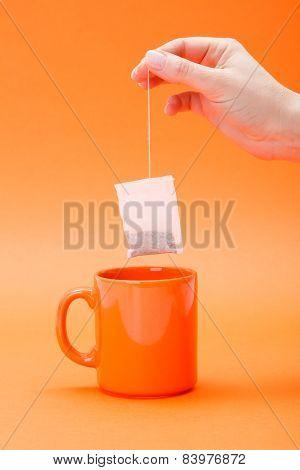 Hand Putting A Tea Bag Into Cup