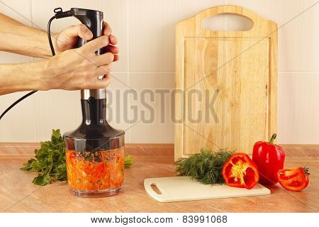 Hands chefs shreded vegetables in blender