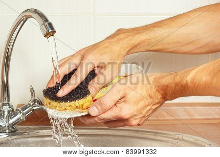 Hands wash the dirty dishes under running water in kitchen