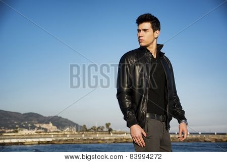 Handsome young man at the seaside overlooking the ocean or sea