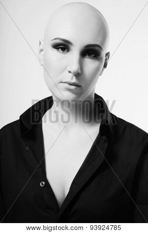 Black and white portrait of young skinhead woman with smoky eyes make-up