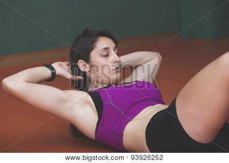 Young woman doing abdominal in the gym poster