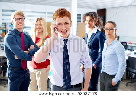 young executive talking phone in multi ethnic teamwork group as leader in office