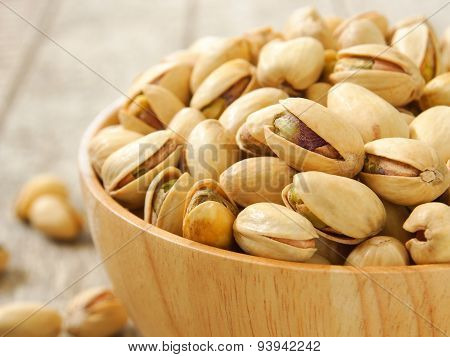 Pistachio nuts in wood cup close up poster
