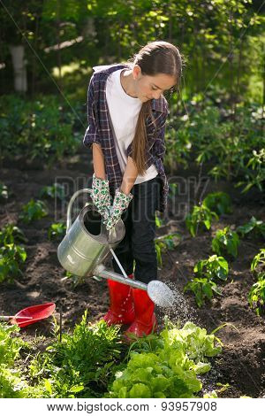 Cute Girl Watering Garden With Watering Can At Hot Summer Day