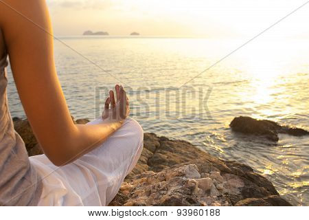 young woman meditation in a yoga pose on the tropical beach