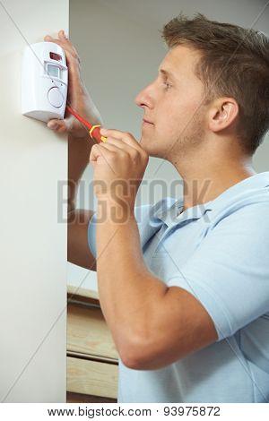 Security Consultant Fitting Burglar Alarm Sensor In Room