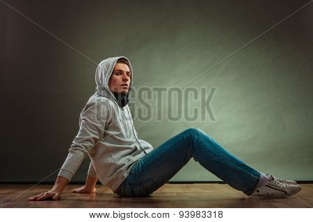 Music passion youth concept. Serious hooded man teen boy with headphones sitting daydreaming on floor grunge background poster