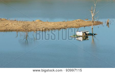 Harmony landscape of Asia countryside lonely floating house on water beautiful Nam Ka lake at Daklak Viet nam. Reflection of dry tree home on river make beautiful scene poster