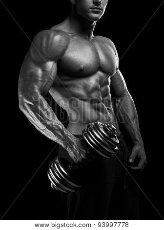Handsome power athletic man with dumbbell confidently looking forward. Strong bodybuilder with six pack perfect abs shoulders biceps triceps and chest poster