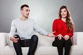 Shy woman and man sitting on sofa couch next each other. First date. Attractive girl and handsome guy meeting dating and trying to talk. Male offering a hand to female. poster