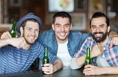 people, leisure, friendship and bachelor party concept - happy male friends drinking bottled beer and hugging at bar or pub poster