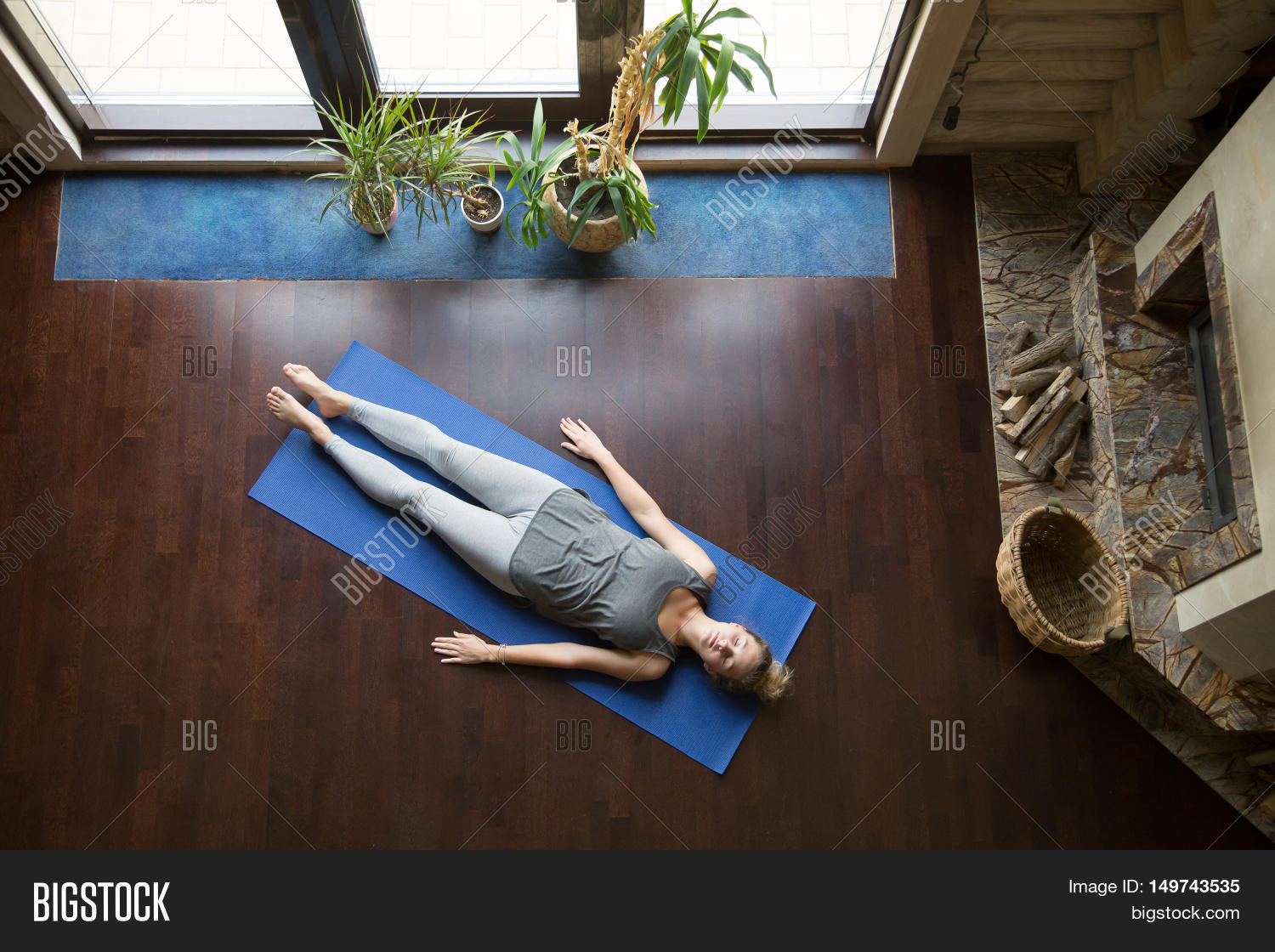 Attractive Young Woman Working Out In Living Room Doing Yoga Exercise On Blue Mat
